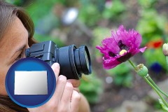 colorado map icon and a female photographer photographing a flower close-up