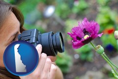 delaware map icon and a female photographer photographing a flower close-up