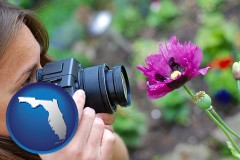 fl map icon and a female photographer photographing a flower close-up