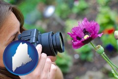 maine map icon and a female photographer photographing a flower close-up
