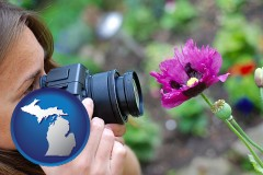 michigan map icon and a female photographer photographing a flower close-up
