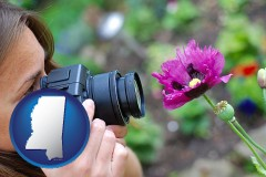 ms a female photographer photographing a flower close-up