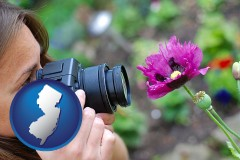nj map icon and a female photographer photographing a flower close-up