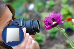 new-mexico map icon and a female photographer photographing a flower close-up