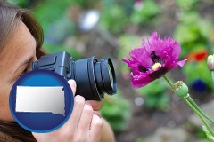 south-dakota map icon and a female photographer photographing a flower close-up