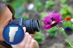 vermont map icon and a female photographer photographing a flower close-up