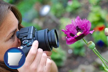 a female photographer photographing a flower close-up - with Arkansas icon