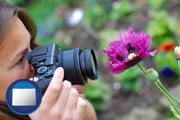 a female photographer photographing a flower close-up - with Colorado icon