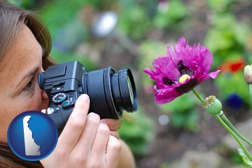 a female photographer photographing a flower close-up - with Delaware icon