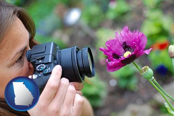 a female photographer photographing a flower close-up - with Georgia icon