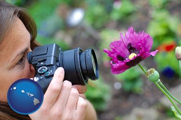 a female photographer photographing a flower close-up - with Hawaii icon