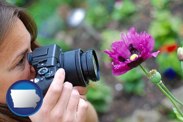 a female photographer photographing a flower close-up - with Iowa icon
