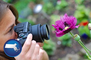 a female photographer photographing a flower close-up - with Massachusetts icon