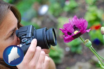 a female photographer photographing a flower close-up - with Maine icon