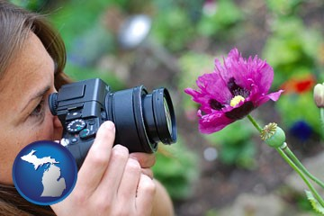 a female photographer photographing a flower close-up - with Michigan icon