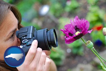 a female photographer photographing a flower close-up - with North Carolina icon