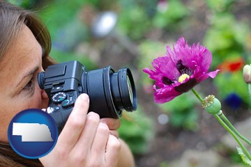 a female photographer photographing a flower close-up - with Nebraska icon