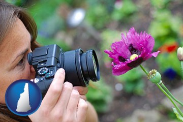a female photographer photographing a flower close-up - with New Hampshire icon