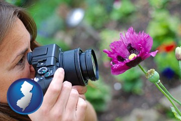 a female photographer photographing a flower close-up - with New Jersey icon