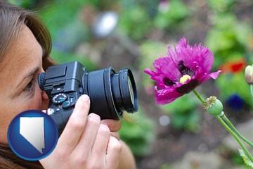 a female photographer photographing a flower close-up - with Nevada icon