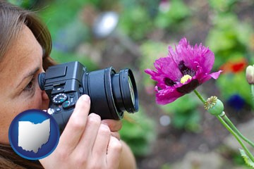 a female photographer photographing a flower close-up - with Ohio icon