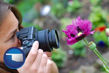a female photographer photographing a flower close-up - with Oklahoma icon