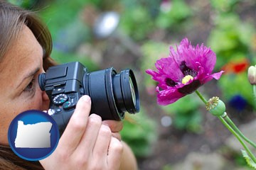 a female photographer photographing a flower close-up - with Oregon icon