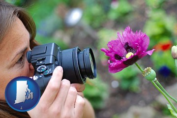 a female photographer photographing a flower close-up - with Rhode Island icon