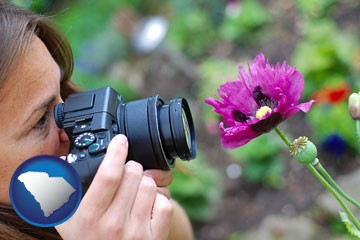 a female photographer photographing a flower close-up - with South Carolina icon