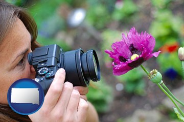 a female photographer photographing a flower close-up - with South Dakota icon