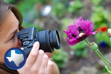 a female photographer photographing a flower close-up - with Texas icon