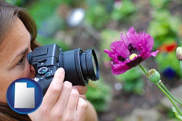a female photographer photographing a flower close-up - with Utah icon