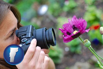a female photographer photographing a flower close-up - with Vermont icon
